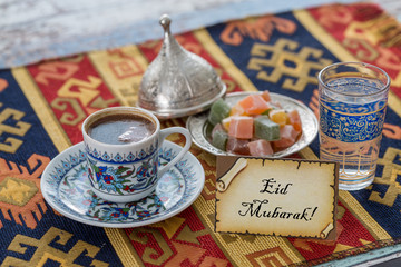 Eid mubarak text  on greeting card with turkish coffee, delights on traditional tablecloth