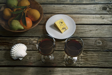 Wine and cheese testing, color grade COLD Red wine, cheese, fruits on outdoor table.
