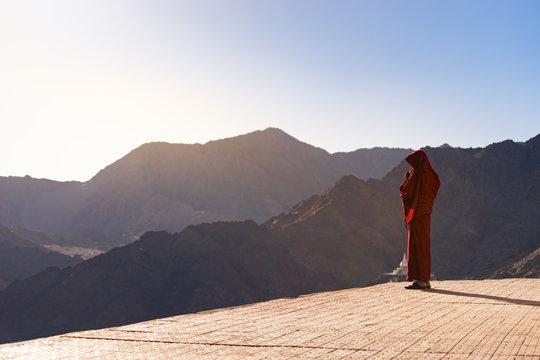 Lama (Tibetan monk) gazing the mountain range and blue sky in Leh Ladakh