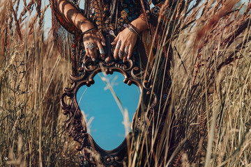 close up of young woman hands holding mirror outdoors