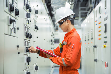 Electrical and Instrument technician checking electrical control board of motor starting system in switch gear room, offshore oil and gas maintenance and service.