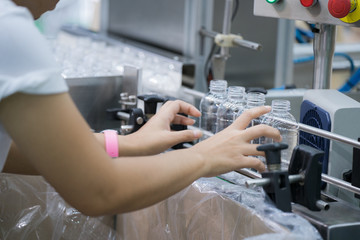 Worker in bottle plastic making working by hand in production line