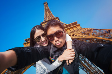 Young couple taking selfie with the Eiffel tower in Paris, France