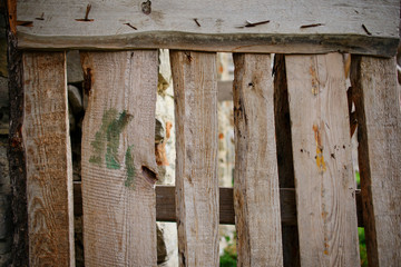 Close up background of vertical fence of light wooden planks that nailed with fasteners and have cracks between each other