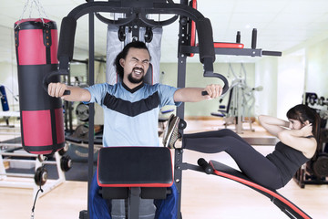 Multiracial people exercising on weights machine