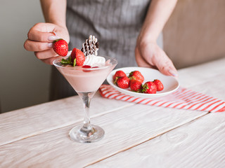 Creamy strawberry dessert in process of decoration by culinary specialist in restaurant. Sweet fruit souffle with fresh red berry, chocolate and mint in martini glass