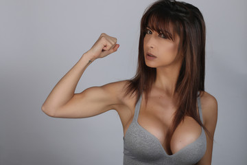 Sexy young brunette woman showing bicep on her arm