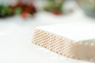 White beaded bracelet on a textile background close up