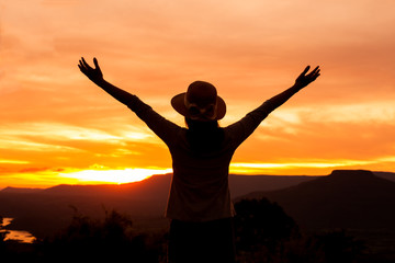 silhouette woman stands on mountain top at sunset time,Freedom happy woman enjoying nature sunset