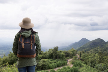 Hipster young woman with backpack enjoying. Tourist traveler on mountain background
