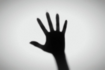Shadow of a hand behind a frosted glass