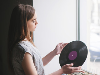 Girl choosing retro vinyl records in music shop. Modern hipster style, young female melomaniac