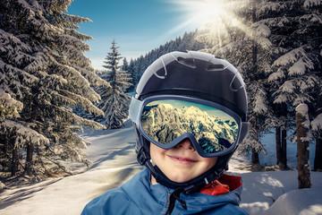 Kind in Winterlandschaft mit Skibrille und Helm