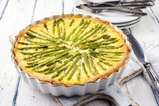 Tart with green asparagus on backing form as top view on wooden table