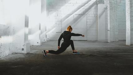 Photo sur Plexiglas Combat Caucasian female in sport outfit practicing karate, Japanese martial arts. Old warehouse indoor shot