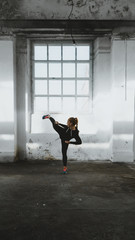 Foto auf AluDibond Kampfsport Caucasian female in sport outfit practicing karate, Japanese martial arts. Old warehouse indoor shot