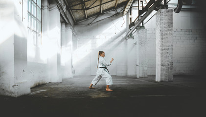 Aluminium Prints Martial arts Caucasian female in Kimono practicing karate, Japanese martial arts. Old warehouse indoor shot