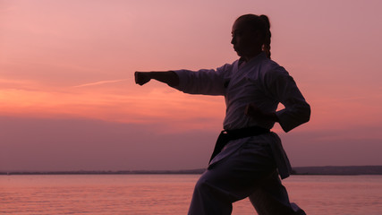 Silhouette of Caucasian female in Kimono practicing karate near large lake on sunset