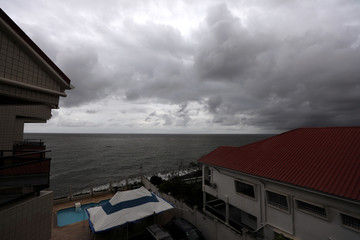 Cloudy sky seen over homes by the seaside in Freetown