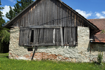 An old barn of village cottages with a walled wall and a wooden roof