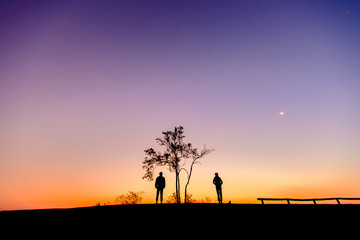 Silhouette of a couple watching beautiful sunrise on the mountain.  beautiful dawn light with copy space. Romantic love concept.
