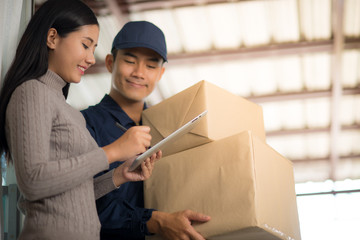 Woman customer signing receipt and receiving the parcel from delivery man. Business and logistic concept.