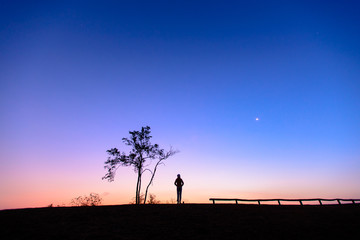 Silhouette of young woman watching beautiful sunrise on the mountain.  Beautiful dawn light with copy space. Romantic love concept.