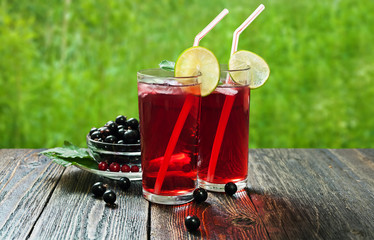Blackcurrant juice with lime in tall glasses on a wooden table