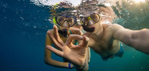 Young couple enjoying snorkeling underwater. Selfie portrait