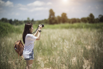 Outdoor summer smiling lifestyle portrait of pretty young woman having fun with camera travel photo of photographer Making pictures