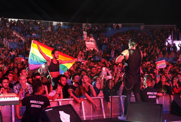 A fan of Lebanese alternative rock band Mashrou' Leila holds a rainbow flag during their concert at the Ehdeniyat International Festival in Ehden town