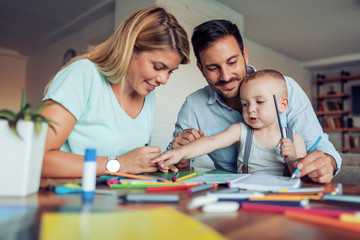 Smiling family drawing together at home