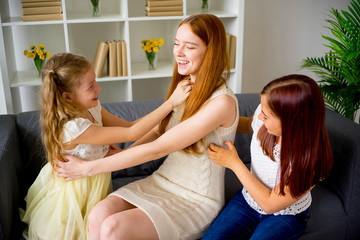 Mother and two daughters playing and tickling
