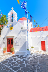 MYKONOS ISLAND, GREECE - MAY 17, 2016: Small square with church building on whitewashed street in beautiful Mykonos town, Cyclades islands, Greece.