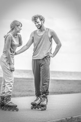 Couple wearing rollerskates looking at each other