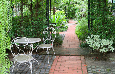White wrought iron table and chairs in tropical garden with bricks paved walkway