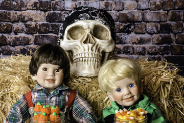 two child dolls with Halloween candy sitting in front of straw bale and human skull