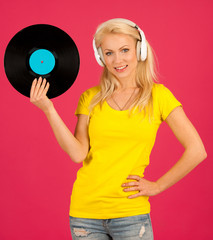 Beautiful young blond woman listening music over vibrant color background