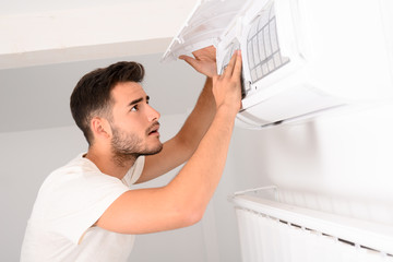 young man electrician installer working and cleaning air filter on a indoor unit air conditioner at client's home