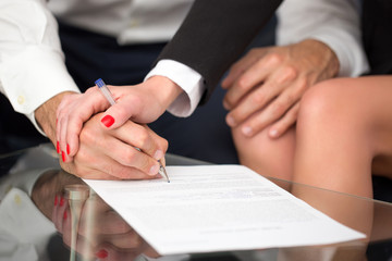 Couple or businesspeople signing contract closeup