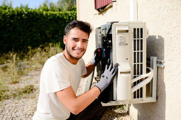 young man electrician installer working on outdoor compressor unit air conditioner at a client's home