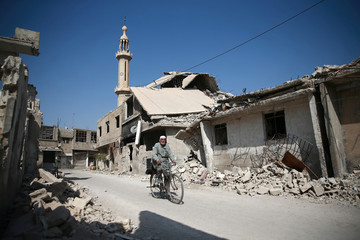 A man rides a bike past rubble of damaged buildings in the rebel-held besieged town of Zamalka