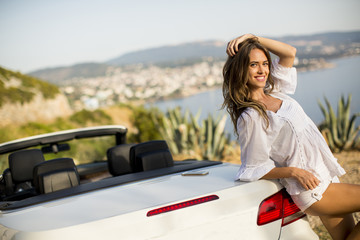Pretty young woman by white cabriolet car