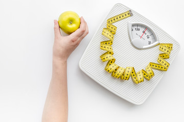 Bathroom scale, measuring tape and apple on white background top view copyspace