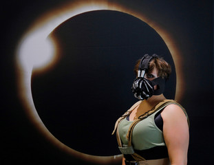 Cassie Gillard, dressed as Lady Bane, poses for a photograph in front of an image of a solar eclipse at the Eclipse Comic-Con in Carbondale