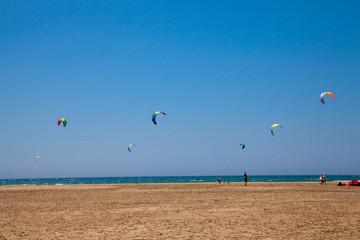 People practicing Kitesurfing. Beach on the peninsula Prasonisi, Rhodes. Colorful kites on the sea shore. Blue sea and windsurfing.