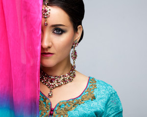 Portrait of beautiful smiling indian girl. Young indian woman model with traditional jewelry set . Indian costume saree