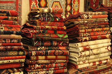 Many turkish rugs folded and stacked in the shop. Close up shot of piled carpets.