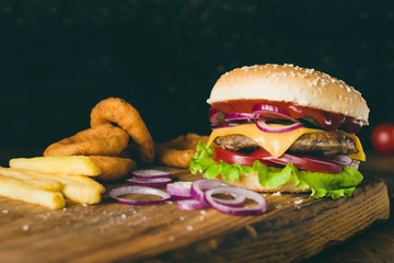 Cheeseburger, french fries and onion rings on wooden cutting board over wooden background. Closeup view, selective focus. Fast food concept