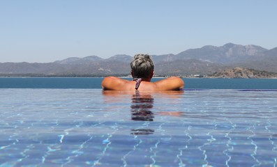 An english lady relaxing in an infinity pool while on vacation in turkey , 2017